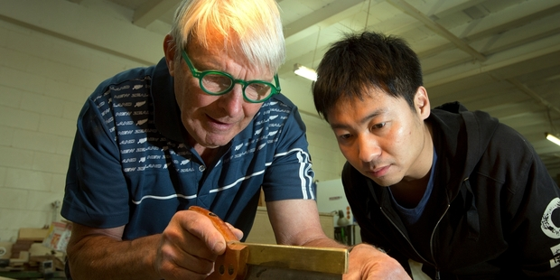 Retired woodwork teacher David Mead, left, shows Evan Pan the finer points of a dovetail joint.